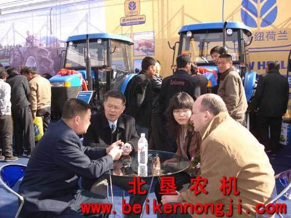 农机展上,上海纽荷兰邓蓝山总经理同已购买4台纽荷兰拖拉机用高清图片